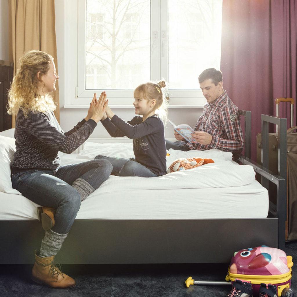 Fotoshooting im a&o Hostel mit einer Familie auf einem Bett.