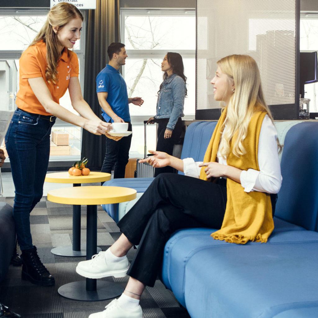 Bildausschnitt von einem Fotoshooting im a&o Hostel mit Service-Mitarbeitern und Gästen im Lounge-Bereich.