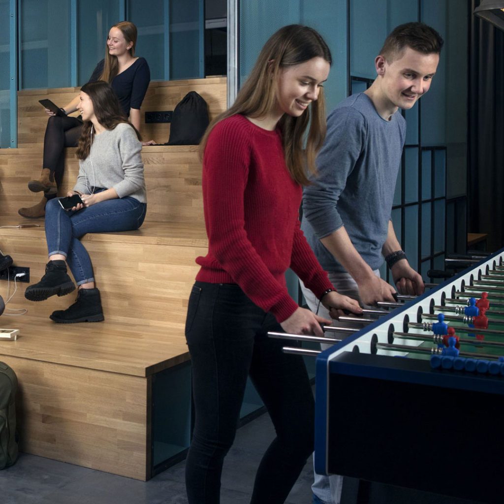 Bildausschnitt von einem Fotoshooting im a&o Hostel mit Tischkicker in der Lobby und jungen Gästen.