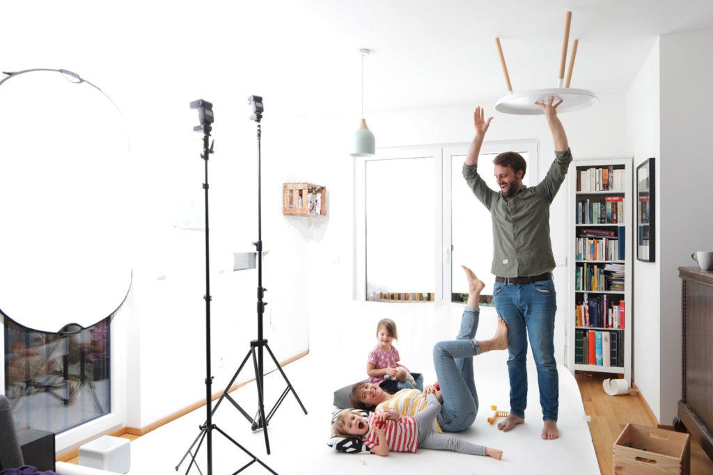 Foto zur Berliner Sparkasse: Abgebildet ist Famile, die Spaß bei einem Fotoshooting haben. Der Vater hält einen Tisch umgekehrt an die Decke, um den Rest zu amüsieren.