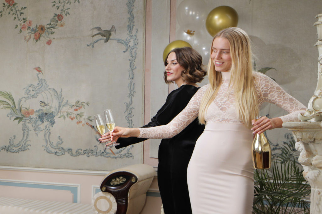 Foto zur Berliner Sparkasse: Abgebildet sind zwei junge Frauen in Abendkleidung, die mit Sektgläsern aus dem Bild schauen.