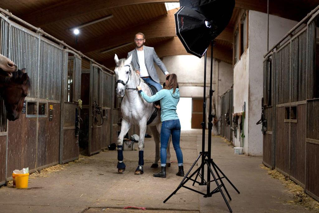Foto zur Berliner Sparkasse: Abgebildet ist ein Blick hinter die Kulissen. Ein Mann auf einem Pferd wird von einer Trainerin geschult.