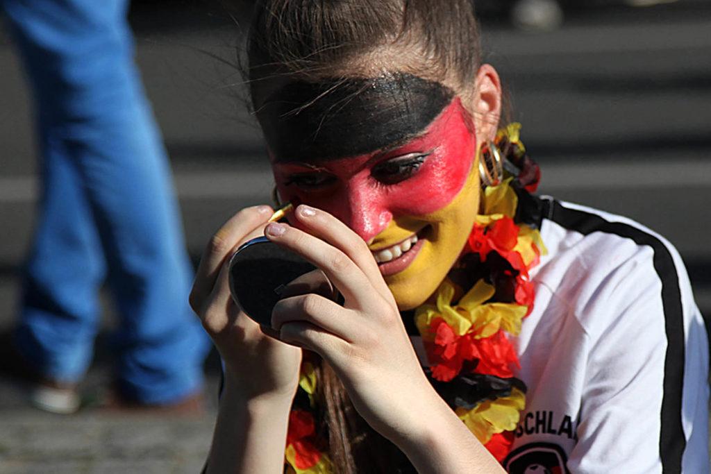 Frau mit Schwarz-Rot-Goldenem Fan-Makeup im gesamten Gesicht.