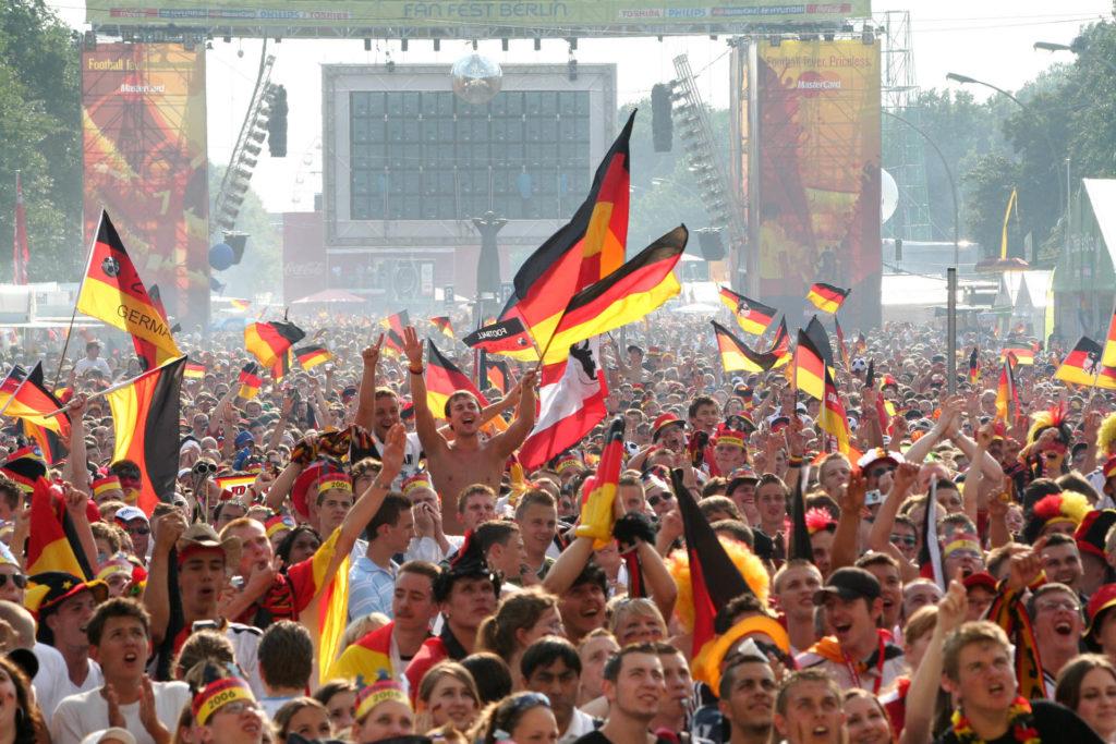 """Jubelnde Menschenmasse mit Deutschland-Flaggen beim Event """"Die Meile"""" zur Fußball-Meisterschaft."""