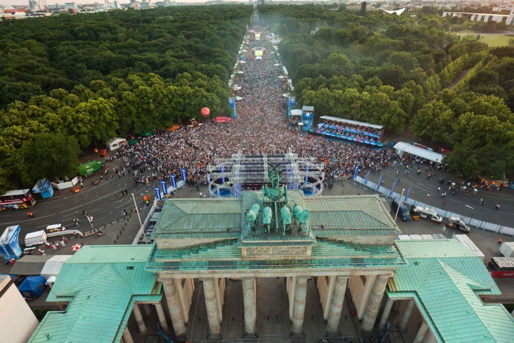 Luftaufnahme vom Brandenburger Tor mit Menschenmasse.