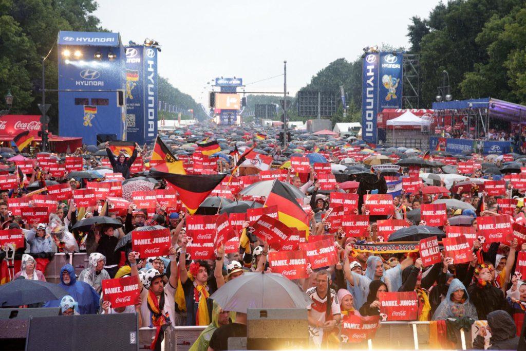 """Menschenmasse mit roten Schildern mit der Aufschrift """"Danke Jungs"""" beim Event """"Die Meile"""" zur Fußball-Meisterschaft."""