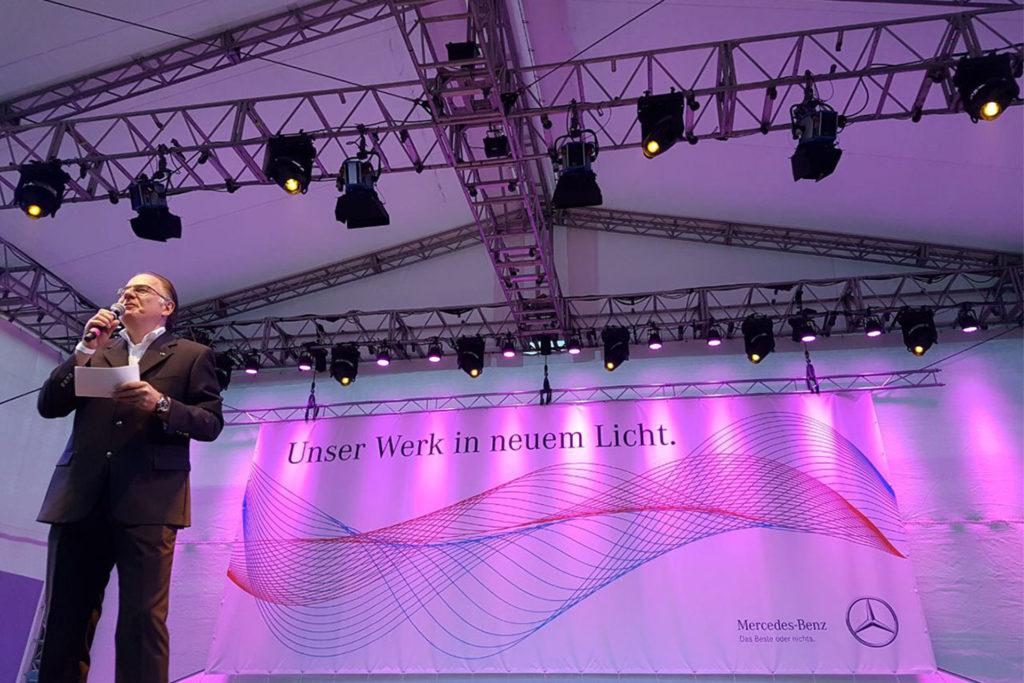 """Bühne bei einem Mercedes-Benz-Event zu der Kampagne """"Unser Werk in neuem Licht"""" mit pinker Beleuchtung und einem Mann mit Mikrofon."""