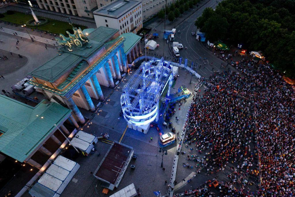 Die Meile: Brandenburger Tor bei Abend mit Musik und Menschenmenge.